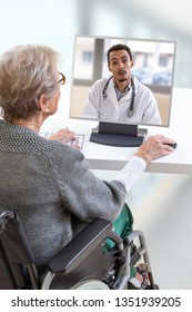 disabled Senior woman consults a e-health doctor with tablet computer sitting on wheelchair . In touchscreen, male doctor: