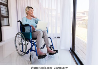 disabled senior woman with laptop relaxing at home