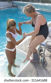 Disabled senior woman with therapist for aqua-gym reeducation