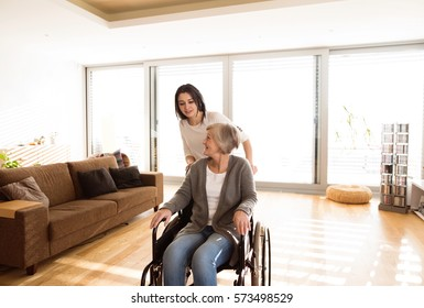 Disabled senior woman in wheelchair with her young daugher.