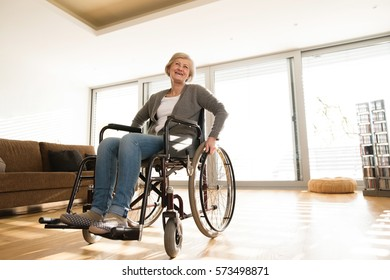 Disabled senior woman in wheelchair at home in living room.