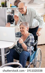 Disabled senior woman in wheelchair waving during a video conference sitting next to husband. paralyzedhandicapped old elderly woman and her husband on online call, using modern communication tech.