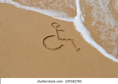 A disabled symbol is drawn in the sand at the beach