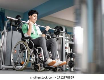 Disabled teenage boy in wheelchair having gym training