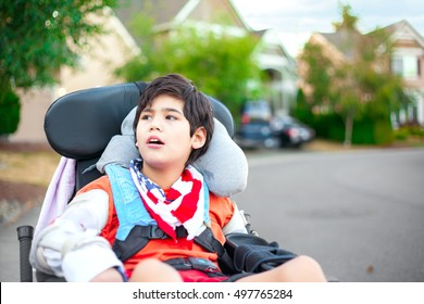 Disabled ten year old boy sitting in wheelchair outdoors looking up into sky, thinking