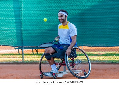 disabled tennis player dribbles with the racket before serving during a match outdoor