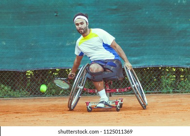 disabled tennis player hits the ball forehand during a match outdoor