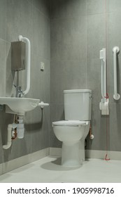 Disabled toilet interior with support and grab rails and emergency pull cord.