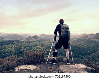 Disabled tourist on crutches on rock. Hurt knee in neoprene metal knee braces and man hold forearms crutches.