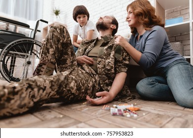 The disabled veteran is depressed. He has problems with drugs. He holds a syringe in his hand. Tablets are lying on the floor. His family is frightened.