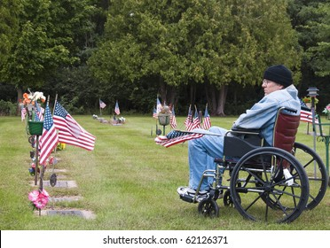disabled veteran in a wheelchair at the cemetery remembering his fallen brothers
