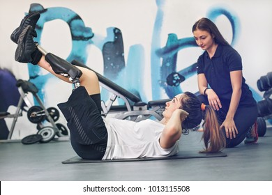 Disabled woman exercising with personal trainer in the gym