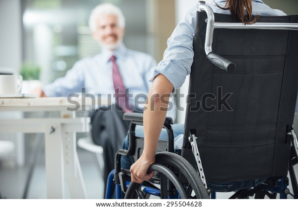 Disabled woman having a business meeting with a businessman rear view, selective focus