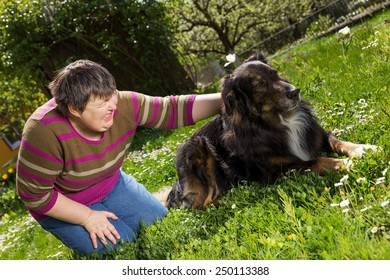 disabled woman on a lawn is stroking a dog