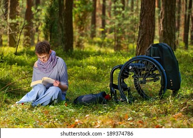 Disabled woman reading a book in the forest, wheelchair