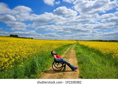 Disabled woman sunbathing on a wheelchair, rape field, spring