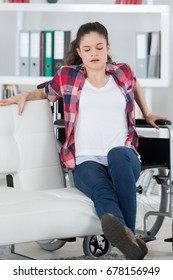 disabled woman trying to sit on sofa by herself