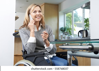 Disabled Woman In Wheelchair Making Call On Mobile Phone At Home