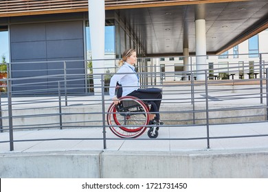 Disabled woman in a wheelchair traveling on a ramp to the business office