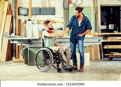 disabled worker in wheelchair in a carpenter's workshop with his colleague in conversation