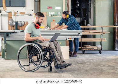 disabled worker in wheelchairwith computer in a carpenter's workshop with his colleague