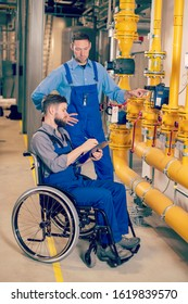 disabled workerwith his colleague in wheelchair in factory