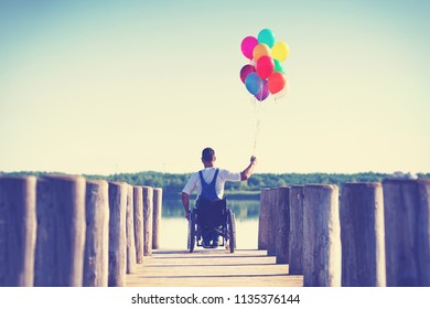 disabled Young man with ballonns in wheelchair on a boardwalk on lake enjoying his freedom