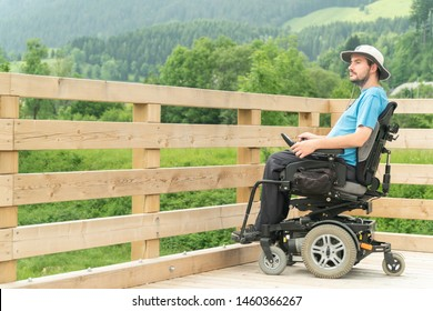 disabled Young man in electric wheelchair on a boardwalk enjoying his freedom and observing nature