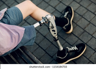 Disabled young man with foot prosthesis sitting outdoor