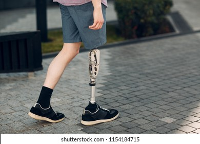 Disabled young man with foot prosthesis walks along the street.
