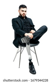 Disabled young man with prosthetic leg, artificial limb concept. Sitting on a chair, isolated on white background