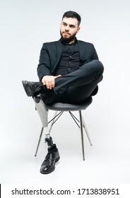 白い背景にスタジオで椅子に義足を持つ身障者の青年、義肢のコンセプ