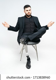 Disabled young man with prosthetic leg sitting on a chair in studio over white background, artificial limb concept