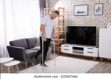 Disabled Young Man Using Crutches To Walk On Carpet