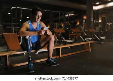 Disabled young man using his mobile in the gym. Disabled sportsman Concept.