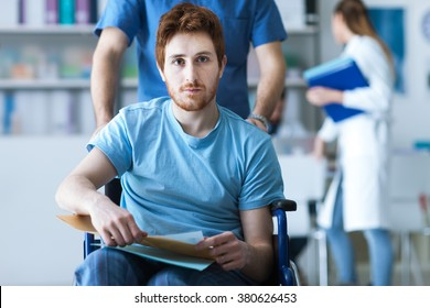 Disabled young man in wheelchair checking his medical records, a male nurse is pushing him, illness and healthcare concept