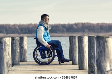 disabled Young man with wheelchair enjoys a sunny day at lake