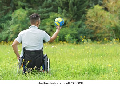 disabled Young man in wheelchair with globe, wheelchair travel concept