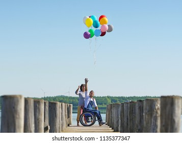 disabled young man in wheelchair with his mother at lake
