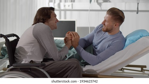 Disabled young man in wheelchair holding hands of sick boyfriend lying in hospital bed. Portrait of man patient lying in bed and talking to friend in wheelchair at hospital ward