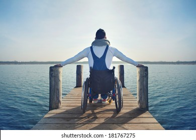 disabled Young man in wheelchair on a boardwalk on lake enjoying his freedom
