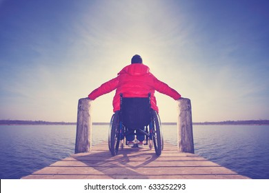 disabled young man in wheelchair on jetty at lake enjoying his freedom