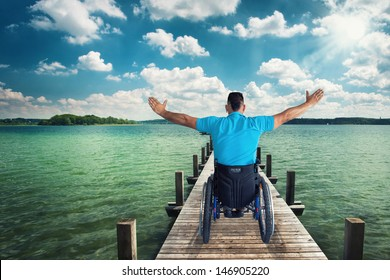 disabled Young man in wheelchair is Standing on an old wooden footbridge and enjoys his freedom,
