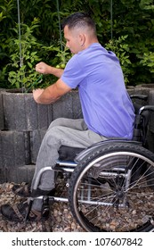disabled young man in wheelchair works outside in garden