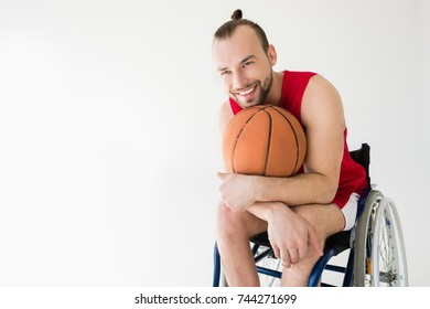 Disabled young sportsman in wheelchair holding basketball ball and looking away, isolated on white