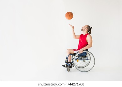 Disabled young sportsman in wheelchair playing basketball and smiling, isolated on grey