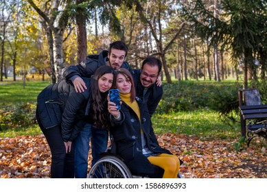 Disabled  young woman taking selfie with her friends in the park on a autumn day