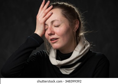 disapointed and confused woman with closed eyes is touching her head by the hand