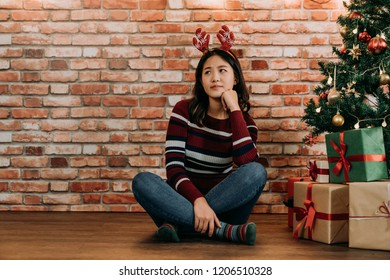 disappoint girl sitting at home alone near the Christmas tree. young girl hasn't be invited to any Xmas party on Christmas eve. teenager concerned about the xmas gifts for friends.