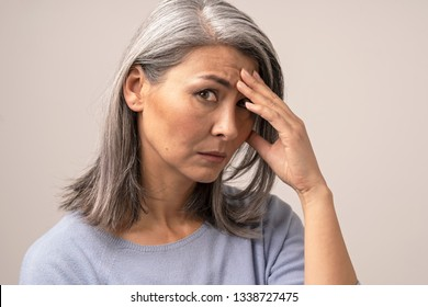 Disappointed Adult Woman of Mongolian Nationality with Gray Hair on a Gray Background. The Sad Look of a Woman Looks into the Frame. She Sadly Puts Her Hand to Her Forehead. Close Up Shoot.